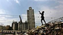 A young boy flies a kite on a garbage heap in Mumbai, India, Monday, Oct. 3, 2011. (Rafiq Maqbool/Associated Press)