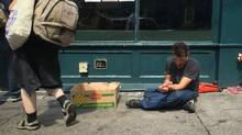 A man, right, injects himself with an unknown substance outside the Insite supervised injection site as a sign is posted warning of heroin cut with fentanyl in the Downtown Eastside of Vancouver. Police say nine people died of overdoses on Thursday night. (DARRYL DYCK For The Globe and Mail)