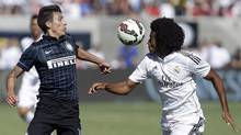 Inter Milan's Ruben Botta, left, and Real Madrid's Derik Osede vie for the ball during the second half of a soccer game in the first round of the Guinness International Champions Cup. (Ben Margot/Associated Press)