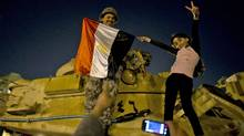 A girl poses with a soldier on top of a tank at Tahrir Square in Cairo early on Feb. 12, 2011. (PEDRO UGARTE/Pedro Ugarte/AFP/Getty Images)