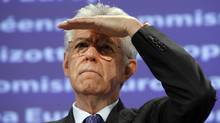 Italian Prime Minister Mario Monti shields his eyes from the light during a joint media conference with European Commission President Jose Manuel Barroso, not shown, at EU headquarters in Brussels, on Tuesday, Nov. 22, 2011. (AP Photo/Virginia Mayo)