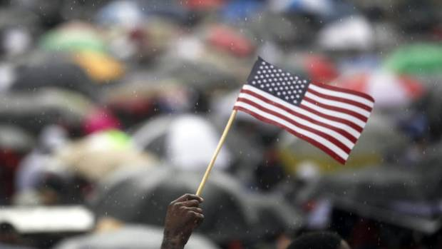 "A demonstrator waves an American flag as it rains during a rally outside the Richard B. Russell Federal Building, Saturday, July 20, 2013, in Atlanta. The Rev. Al Sharpton's National Action Network organized ""Justice for Trayvon"" rallies nationwide to press for federal civil rights charges against George Zimmerman, who was found not guilty in the shooting death of unarmed teenager Trayvon Martin. (Jaime Henry-White/AP)"