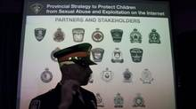 A police officer walks past a projection of the Ontario Police services that participated in a province-wide investigation targeting child pornography offenders following a media conference in Vaughan, Ontario on Thursday, February 2, 2012. (Pawel Dwulit/Pawel Dwulit/The Canadian Press)