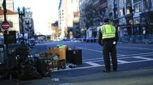 A day after the Boston Marathon, a police officer stands on Boylston Street at the finish line near the site of two explosions, in Boston, April 16, 2013. On Tuesday a mile-square area of downtown Boston remained cordoned off as a crime scene, and officials still had no one in custody after at least three people were killed and more than 140 were injured, some of them having lost limbs and suffered grievous wounds. (ERIC THAYER/NYT)