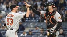 Baltimore Orioles relief pitcher Zach Britton high-fives catcher Matt Wieters after defeating the New York Yankees on Oct. 2, 2016. The Orioles' win gave them a wild card playoff spot. (Kathy Kmonicek/The Associated Press)