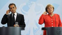French President Nicolas Sarkozy, left, and German Chancellor Angela Merkel at a news conference in Berlin Friday. (FABRIZIO BENSCH/REUTERS)