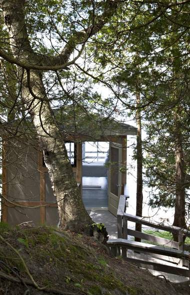 The richness and complexity of the interior design of this Beaverton, Ont. cottage perched above the eastern shore of Lake Simcoe is hinted at even before entering. High double gates, dressed up in blackened bamboo neatly tied with twine, mark entry to the property. Seen here - the boathouse. (Andrew Filarski)