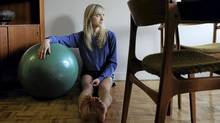 Emily Nicholas, 29, is photographed exercising with her yoga ball in her Toronto home on Dec 20 2011. After a stress fracture in her leg was misdiagnosed, she eventually broke it in a fall and has since undergone several operations to correct the problem. (Fred Lum/Fred Lum/The Globe and Mail)