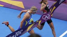 Switzerland's Nicola Spirig, right, finishes ahead of Sweden's Lisa Norden to win the gold medal in the women's triathlon at the 2012 Summer Olympics, Saturday, in London. Norden took the silver. (Charlie Riedel/AP)