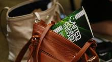 The handbook United Against Terrorism - A Collaborative Effort Towards A Secure, Inclusive and Just Canada sticks out of a purse during a press conference at Winnipeg Central Mosque in Winnipeg, Monday, September 29, 2014. (JOHN WOODS/THE CANADIAN PRESS)