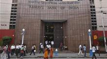 People walk in front of the Reserve Bank of India (RBI) building in Kolkata May 21, 2012. (RUPAK DE CHOWDHURI/REUTERS)
