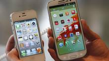 An employee poses as he holds Apple's iPhone 4s, left, and Samsung's Galaxy S III at a store in Seoul in this August 24, 2012 file photo. (LEE JAE-WON/REUTERS)