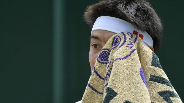 Kei Nishikori of Japan wipes his face during his men's singles tennis match against Andreas Seppi of Italy at the Wimbledon Tennis Championships, in London June 29, 2013. (TOBY MELVILLE/REUTERS)