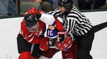 Team Canada's Meghan Agosta, left, wrestles with Team Russia's Yevgenia Dyupina during third period action at the World Women's Ice Hockey Championships Tuesday, April 10, 2012 in Burlington, VT. Canada won the game 14-1. (Ryan Remiorz/THE CANADIAN PRESS)