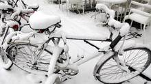 Snow covers bicycles in Antwerp, Belgium, last week. As cold, snowy weather afflicts much of Europe and North America, parts of the Far North are experiencing one of the warmest winters on record. (Virginia Mayo/AP)