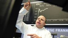 A broker views his monitor at the Stock Exchange in Frankfurt, Germany, Wednesday, Jan. 2, 2013. Financial markets worldwide eased after the United States averted the so-called fiscal cliff. (Arne Dedert/AP)