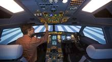 A technician operates a CAE-built A330-200 passenger plane flight simulator at the Lufthansa Flight Training (LFT) centre in Berlin, November 1, 2012. Montreal-based CAE announced the sale of five flight simulators on Wednesday as part of several new military and commercial contracts worth a total of $215-million. (THOMAS PETER/REUTERS)