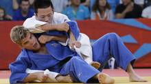 Wang Ki-chun of South Korea, top, competes with Nicholas Delpopolo of the United States during the men's 73-kg judo competition at the 2012 Summer Olympics, Monday, July 30, 2012, in London. (Associated Press)