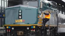 A Via Rail employee climbs aboard an F40 locomotive at the train station in Ottawa on Monday, December 3, 2012 (Adrian Wyld/THE CANADIAN PRESS)