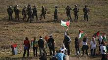 Palestinians demonstrate against the expansion of the nearby Jewish settlement of Halamish as Israeli forces stand by in the West Bank village of Nabi Saleh near Ramallah, Friday, Dec. 16, 2011. (AP Photo/Majdi Mohammed/AP Photo/Majdi Mohammed)