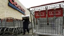 A shopper carries her goods from a Costco Wholesale store in Arlington, Va. (RICHARD CLEMENT/REUTERS)