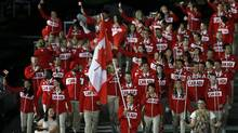 Canada's flag bearer Simon Whitfield holds the national flag as he leads the contingent in the athletes parade during the opening ceremony of the London 2012 Olympic Games at the Olympic Stadium July 27, 2012. (PHIL NOBLE/REUTERS)