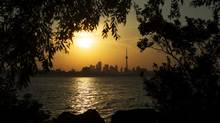 The sun rises over the CN tower and the skyline in Toronto on July 19, 2013. (MARK BLINCH/REUTERS)