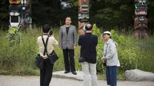 Tourists from China check out the totem poles in Vancouver's Stanley Park on Thursday. (John Lehmann/The Globe and Mail)