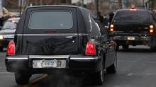 A hearse bears away the body of 6-year-old Noah Pozner after his funeral. Noah was killed when a gunman walked into Sandy Hook Elementary School in Newtown, Conn., and opened fire, killing 26 people, including 20 children. (Jason DeCrow/AP)