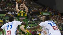 Brazil's Marcelinho Huertas, center, shoots over France's Florent Pietrus, left, and Boris Diaw, right, during the Group A Basketball World Cup match between Brazil and France in Granada, Spain (DANIEL TEJEDOR/AP)