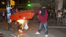 A man tries to burn a a plastic barricade during the riot in Vancouver June 15, 2011. (John Lehmann/ The Globe and Mail/John Lehmann/ The Globe and Mail)