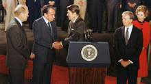 U.S. President Ronald Reagan, behind podium, shakes hands with former President Richard Nixon as former presidents Gerald Ford, left, and Jimmy Carter look on at the White House in Washington, D.C., in this Oct. 8, 1981 file photo. (AP)