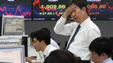A currency trader reacts in front of screens showing the Korea Composite Stock Price Index. (Ahn Young-joon/AP)