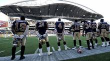 Winnipeg Blue Bombers quarterback Buck Pierce (4) and teammates stand for the anthem during the first game at Investors Group Field in Winnipeg, June 12, 2013. (FRED GREENSLADE/REUTERS)