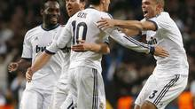 Real Madrid's Pepe (R), Xabi Alonso and Michael Essien (L) celebrate with teammate Mesut Ozil (2nd R) after he scored a last minute equalizing goal against Borussia Dortmund during their Champions League Group D soccer match at Santiago Bernabeu stadium in Madrid November 6, 2012. (JUAN MEDINA/REUTERS)
