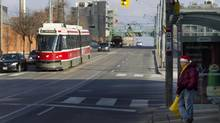 A man wearing a Santa hat waits for an eastbound streetcar on Queen Street East. (Peter Power/The Globe and Mail)