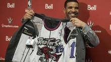 Hip Hop Star and MLSE ambassador Drake shows off the lining of his suit during a press conference before the Toronto Raptors' NBA game against Brooklyn Nets in Toronto on Saturday January 11 , 2014. (Chris Young/THE CANADIAN PRESS)