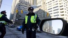 Toronto Police officers direct traffic after a power outage in Yorkville. The city's budget chief eviscerated Toronto?s approach to hiring off-duty police for special events and construction zones on Tuesday, calling the $29-million Toronto spends on the such assignments ?out of hand? (Darren Calabrese/Darren Calabrese for The Globe and Mail)