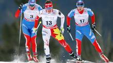 Ivan Babikov, right, from Canmore, Alta., leads Russia's Evgeniy Belov, left, during the men's World Cup 30-km Skiathlon in Canmore, Alta., Sunday, Dec. 16, 2012. (Jeff McIntosh/THE CANADIAN PRESS)