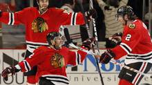 Chicago Blackhawks' Kris Versteeg, lower left, celebrates with Duncan Keith, right, and Andrew Ladd after scoring against the Vancouver Canucks during the third period of Game 2 of an NHL hockey Western Conference second-round playoff series Monday, May 3, 2010, in Chicago. The Blackhawks won 4-2. (AP Photo/Nam Y. Huh) (Nam Y. Huh)