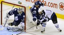 Winnipeg Jets forward Jim Slater (R) tries to get a shot on Toronto Maple Leafs goalie James Reimer while being checked by defenseman Carl Gunnarsson (C) during the first period of their NHL hockey game in Toronto October 19, 2011. (MIKE CASSESE/REUTERS)