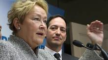 Quebec Premier Pauline Marois gestures as she announce the party's stand on the provincial debt as Quebec treasury board chair Stephane Bedard, Wednesday March 12, 2014 in Quebec City. (CLEMENT ALLARD/THE CANADIAN PRESS)