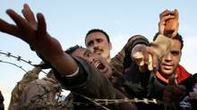 Men reach for bread behind barbed wire while waiting to enter Tunisia after fleeing Libya on February 28, 2011 in Ras Jdir, Tunisia. (Spencer Platt/Getty Images/Spencer Platt/Getty Images)