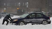 A passenger pushes a car in a parking lot in Halifax on Sunday, Dec.15, 2013. The storm is expected to dump up to 30 centimetres of snow on the region. (Andrew Vaughan/THE CANADIAN PRESS)