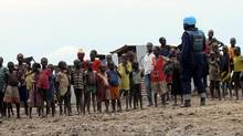 A UN peacekeeper stands watch as children look on at a camp for displaced civilians in Bentiu, South Sudan, on June 18, 2017. (STAFF/REUTERS)