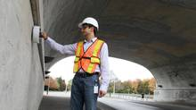 Aali Alizadeh, CEO of Giatec Scientific, tests concrete durability on the Bank Street bridge in Ottawa. Giatec has found customers in 10 countries who are interested in its patented handheld device. (Dave Chan for The globe and mail)