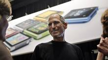 Apple CEO Steve Jobs smiles in front of an iPod Shuffle poster, Wednesday, Sept. 1, 2010, in San Francisco. (Paul Sakuma/AP)