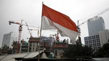 An Indonesian flag seen near a construction site in Jakarta, Indonesia, on Feb. 17. The Jakarta index tumbled into a bear market and the currency sank to a 17-year low in 2015. (DARREN WHITESIDE/REUTERS)