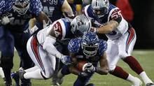 Montreal Alouettes' Kyries Hebert and Gabriel Knapton can't stop Winnipeg Blue Bombers' Nic Grigsby during the second half of CFL action in Winnipeg (JOHN WOODS/THE CANADIAN PRESS)