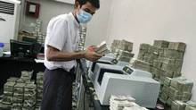 A bank employee counts Myanmar kyat banknotes: More than two decades of isolation and poor government have left Myanmar the poorest country in Asia besides Afghanistan. (Reuters/Reuters)